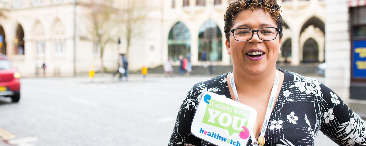 Healthwatch staff member holding an It Starts With You sign to promote the campain